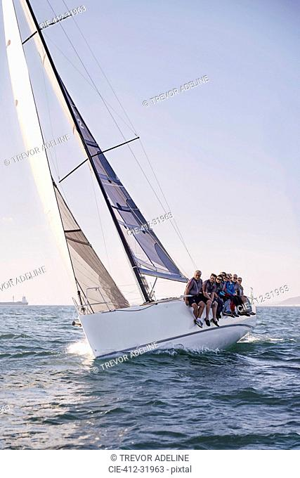 Friends sailing on heeling sailboat on ocean under blue sky