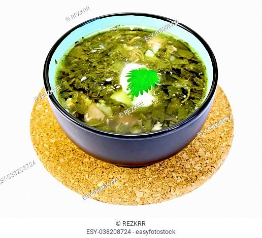 Green nettle soup in a bowl on a stand cork isolated on white background