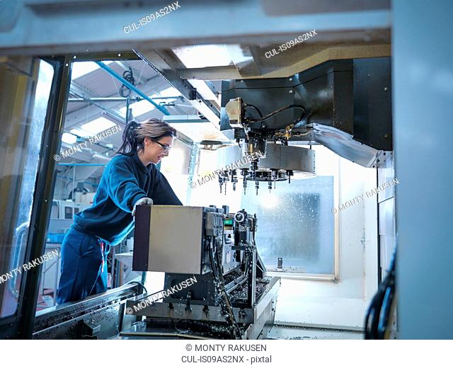Female apprentice engineer setting up CNC lathe in engineering factory