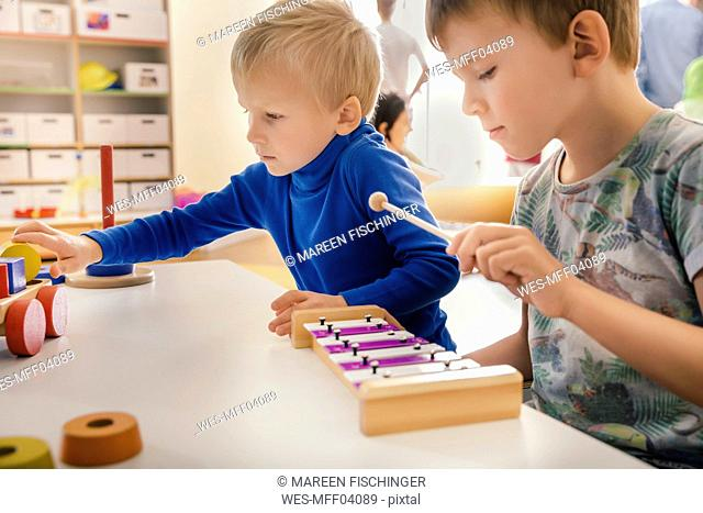 Two boys playing with musical instruments and toys in kindergarten