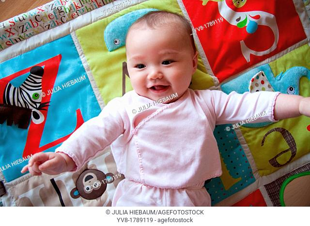 Happy baby on colorful playmat