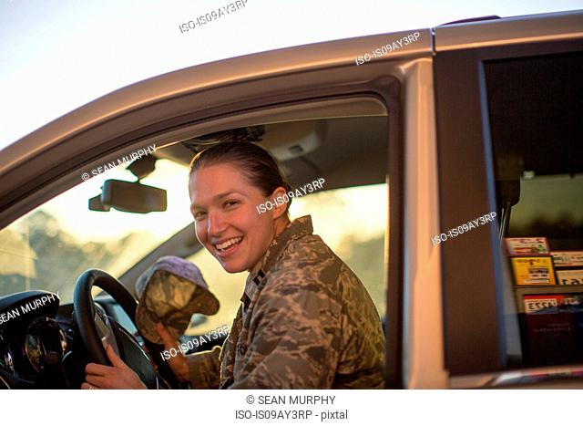 Portrait of female soldier sitting in car at air force military base