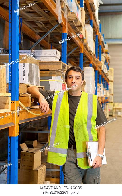 Hispanic worker holding clipboard in warehouse