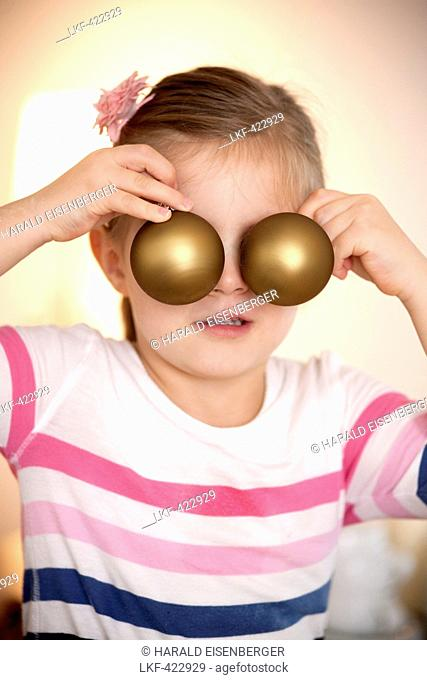 Girl (4 years) covering eyes with two christmas tree balls, Styria, Austria