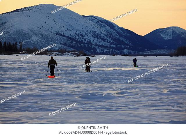 A group of men travel the Stikine River while pulling sleds with gear in the late afternoon as the light begins to fade with Farm Island in the background