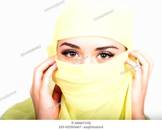 Asian girl with brown eyes posing in a yellow scarf, muslimah model in hijab isolated in white background