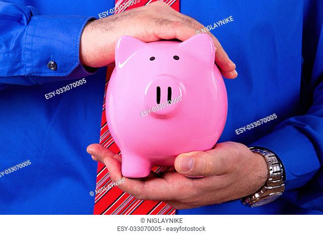 Businessman with blue shirt covering and protecting pink piggy bank with his hands