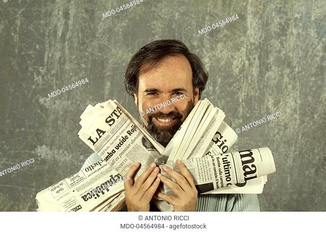 Television writer Antonio Ricci holding some newspapers in his hands. Cologno Monzese, Italy. May 1991