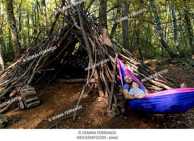 Father and daughter lying together in hammock in a forest