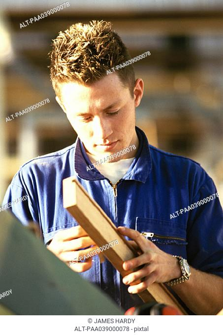Man in coveralls, holding plank