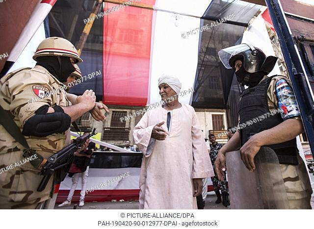 20 April 2019, Egypt, Cairo: Army soldiers guide a voter to the way inside a polling station during the first day of the national referendum on the...