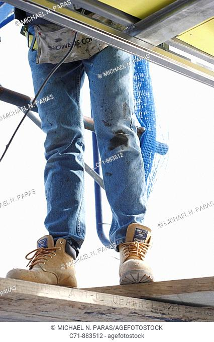 Construction worker from below standing on wood planking