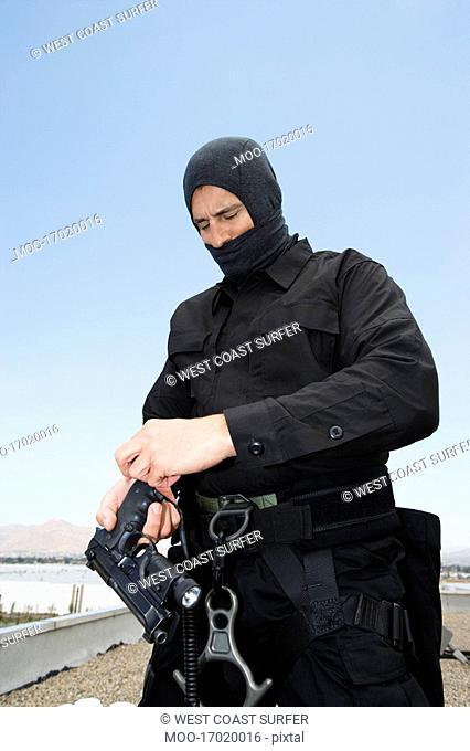 SWAT Team Officer Loading Pistol