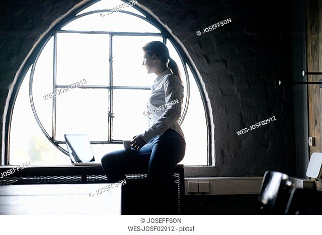 Businesswoman with laptop and cup of coffee at the window