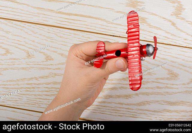 Hand holding a red toy plane on a on wooden texture