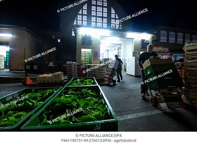 23 July 2019, Bavaria, Munich: Heads of lettuce are stuck in a box in front of Hall 1 of the Munich wholesale market. At the Munich wholesale market