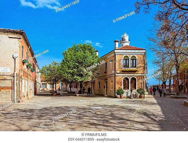 Daylight view to green square with trees and people walking. Historic architecture buildings and bright blue sky with clouds