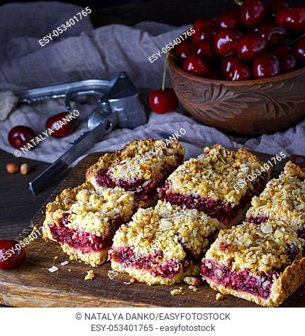 square pieces of cake crumble on brown wooden board, top view