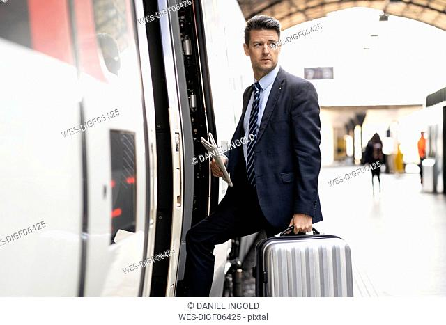 Businessman with suitcase getting in train