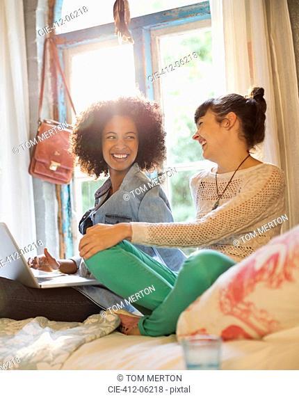 Women relaxing together in bedroom