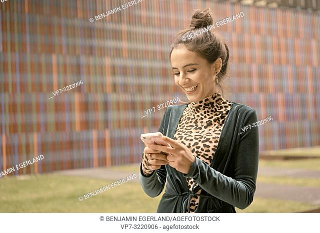 laughing woman using smartphone