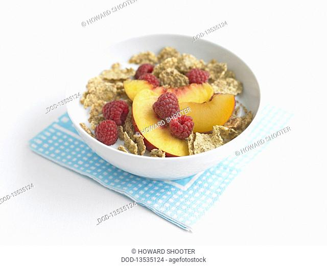 Bran flakes and fruits in bowl with milk, close-up
