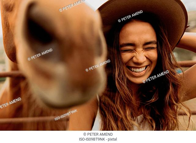 Young woman in felt hat laughing next to horse, Jalama, California, USA