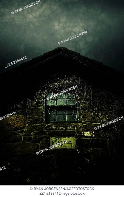 Night vertical image of an abandoned house with spooky attic window and creeping vines