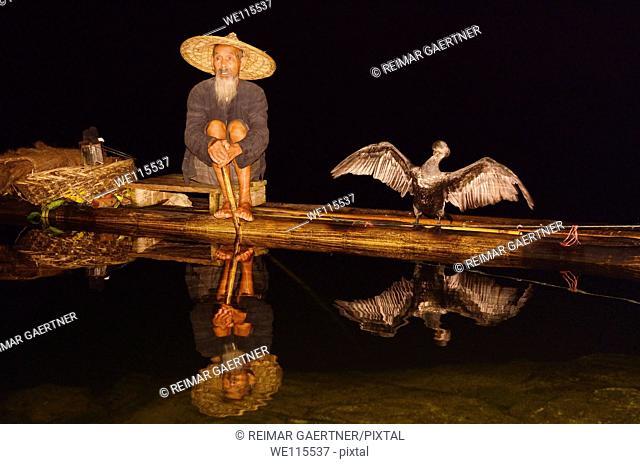 Cormorant fisherman and bird reflected in a calm Li river at night from a bamboo raft Huangbutan China