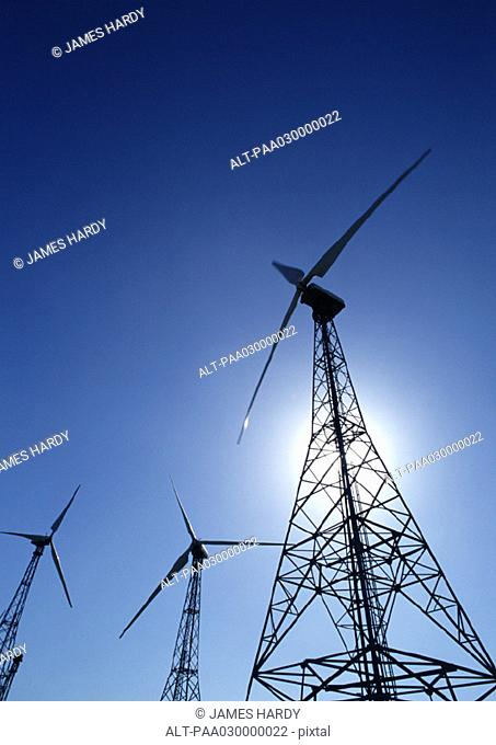 Wind turbines, low angle shot, blue sky and hazy sun in background
