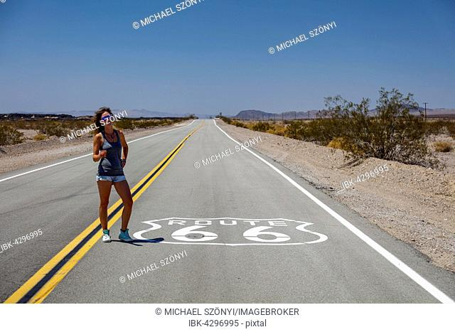 Young woman on the road Route 66, Needles, Mojave Desert, California, USA