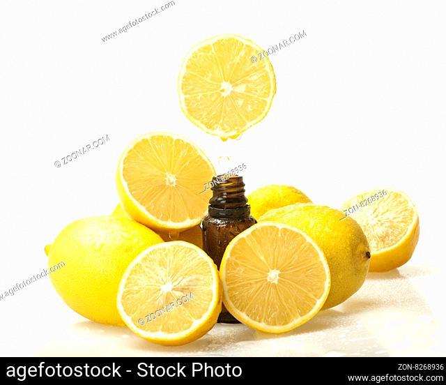 Lemon essential oil and lemon fruits on white background