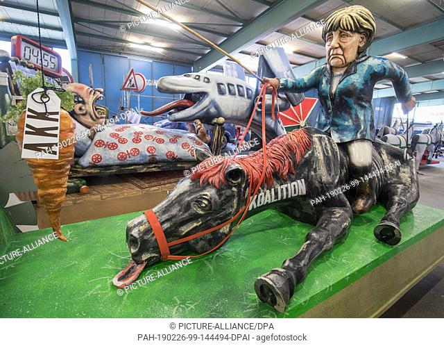 """26 February 2019, Rhineland-Palatinate, Mainz: Chancellor Merkel sits on the """"""""coalition ridden to death"""""""" at the presentation of the Mainz Carnival..."""