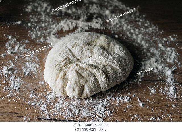 Fresh bread dough on floured wooden surface