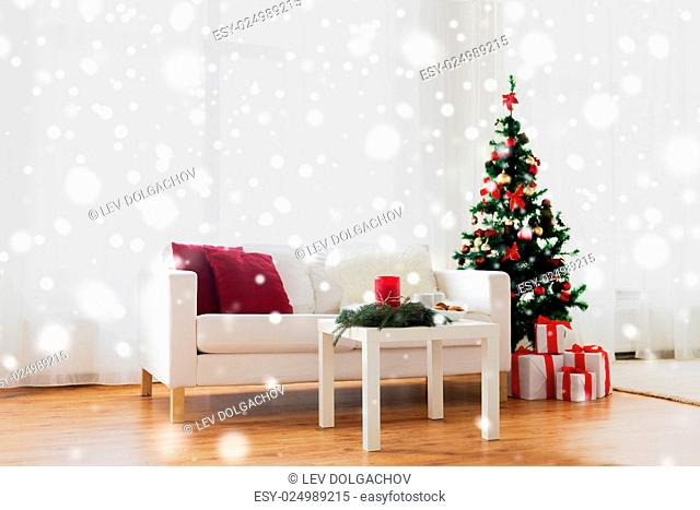 holidays, celebration, decoration and interior concept - sofa, table and christmas tree with gifts at home