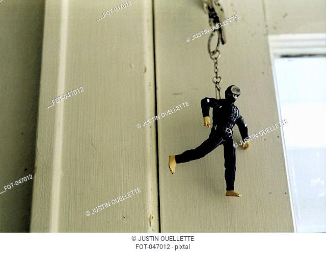 A scuba diver keychain hanging from a door lock