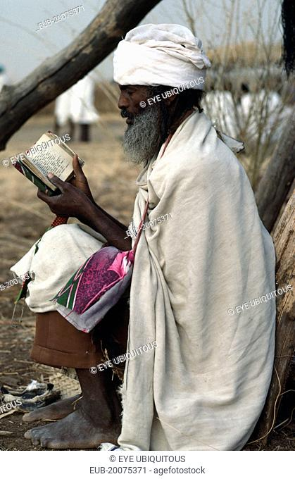 Amhara Ethiopian orthodox priest reading from book in refugee settlement