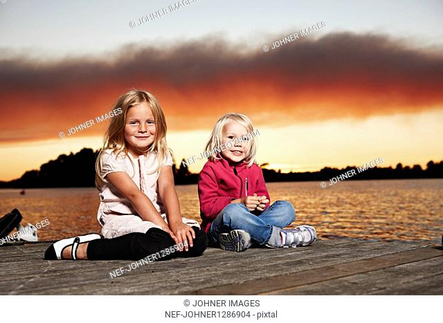 Portrait of two girls sitting on jetty at sunset