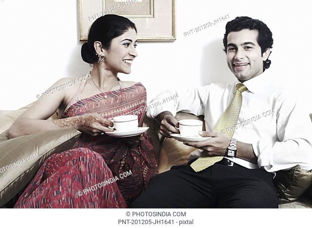 Close-up of a young couple holding cups of tea