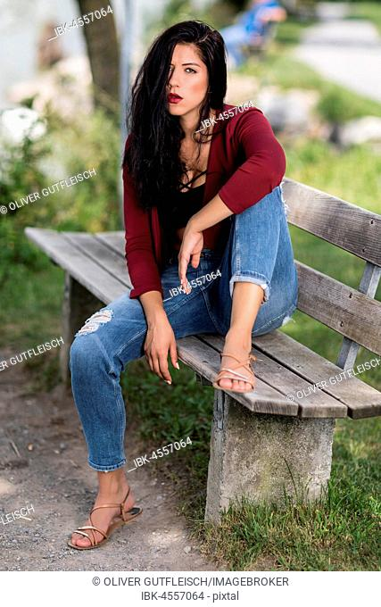 Young woman with a wine-red jacket and blue jeans sitting on a wooden bench