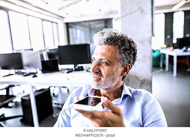 Portrait of mature businessman using smartphone in office