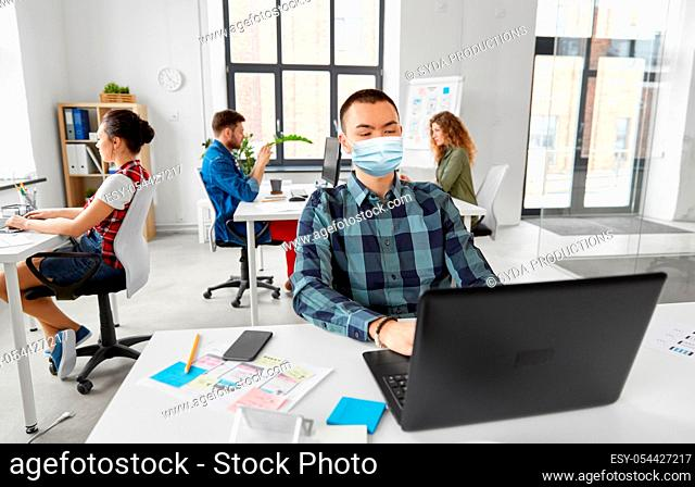 man in medical mask with laptop working at office