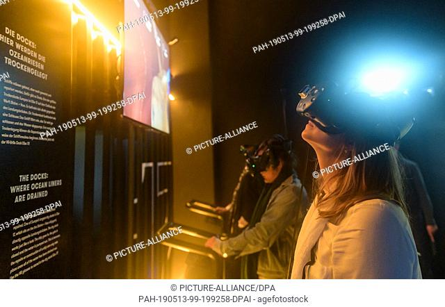 13 May 2019, Hamburg: Visitors of the Discovery Docks with Virtual Reality glasses watch information monitors at the opening of the harbour experience world...