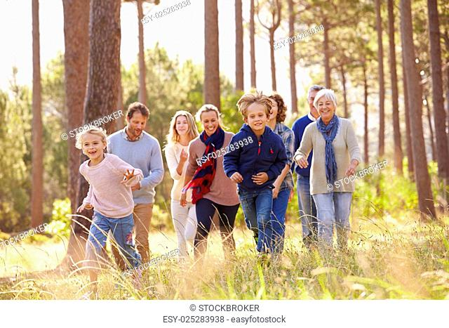 Multi-generation family walking in countryside, kids running