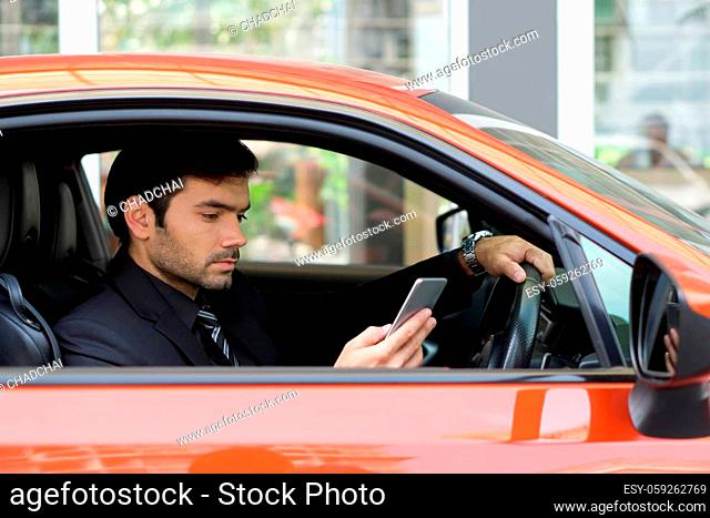 Young businessman in a black suit look at mobile phone while holding the car wheel