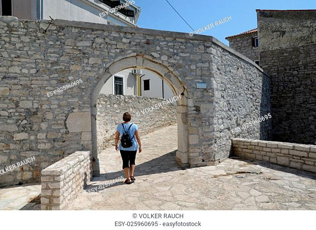 novigrad,istria,croatia,location,town,coast,sea,mediterranean sea,old town,woman,person,human being,ramparts,wall,gate,gate,passage