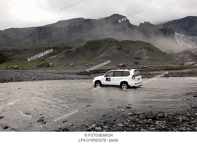 SUV driving across a shallow river belowa misty mountain range
