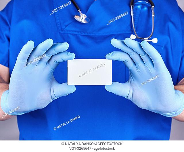 male doctor wearing blue latex gloves is holding a blank white paper business card, close up
