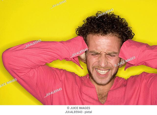 Man covering ears with hands