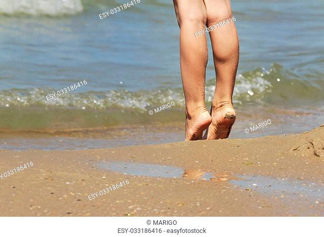 Healthy toned athletic legs of man on the coast in Sunny weather